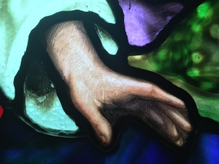 Close-up of Jesus' hand portrayed in Rainbow's stained glass window.